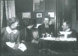 Tre unge kvinner og to unge menn i stueinteriør. Harald Rydg