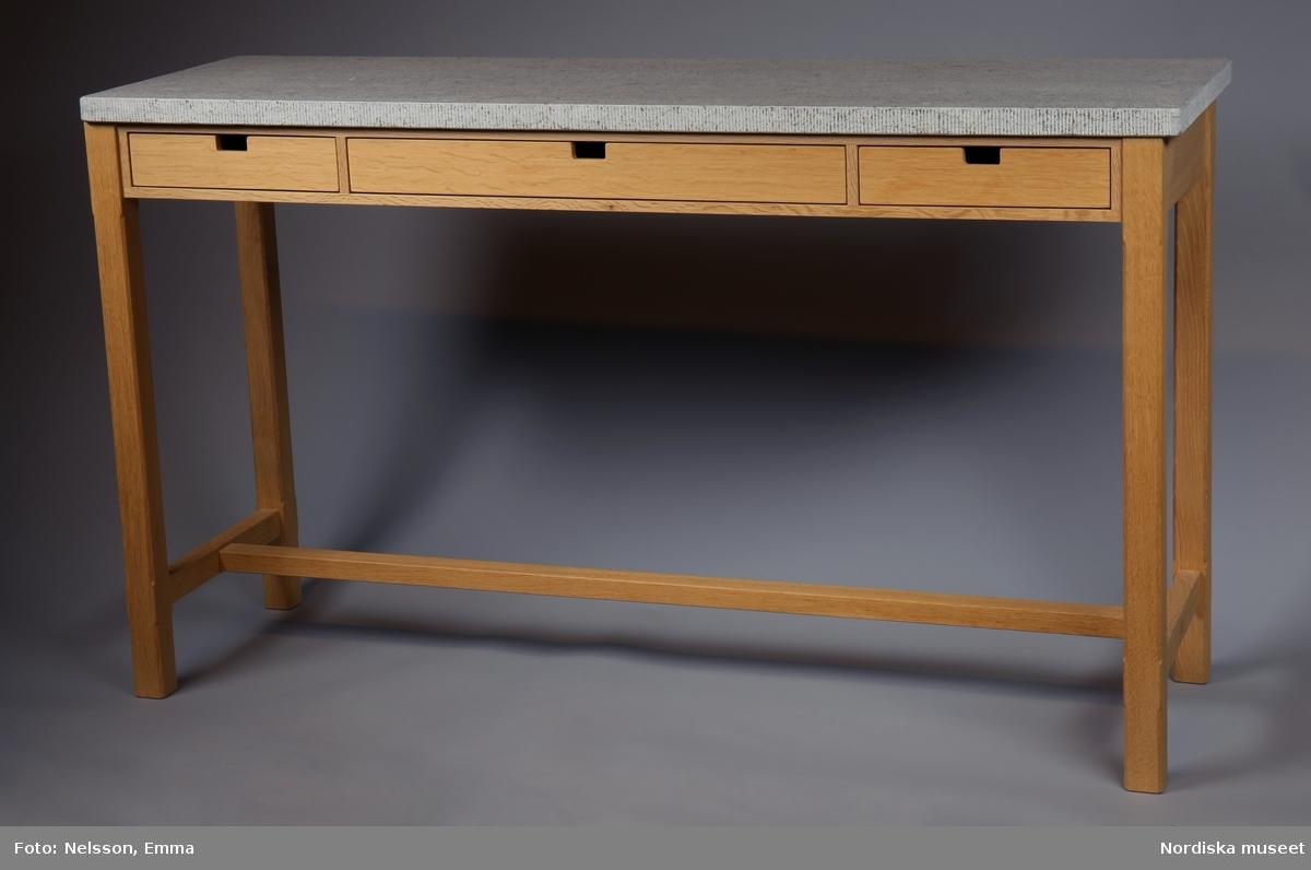 """a) Sideboard, """"Pappi"""", 2002, av såpad massiv ek med skiva av grå hyvlad kalksten. Formgivet 1994 av Kerstin Olby, Olby Design AB. Rektangulär, rak form med benkryss. Fasade ben.  b:1-3) Tre lådor i sargen. Lådsidor av massiv björk, lådbottnar av björkplywood.   Förtryckt etikett med handskriven text i en av lådorna, bland annat """"Tillverkad av I.C."""" [=Ingmar Carlson, möbelsnickare]. /Anna Arfvidsson Womack 2021-08-19"""