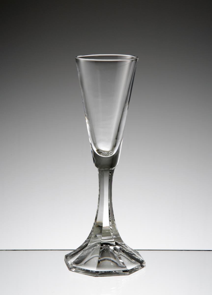 Formgivare: Nils Landberg. Brännvinsglas. Konisk kupa, fasettslipat luftben och fot.