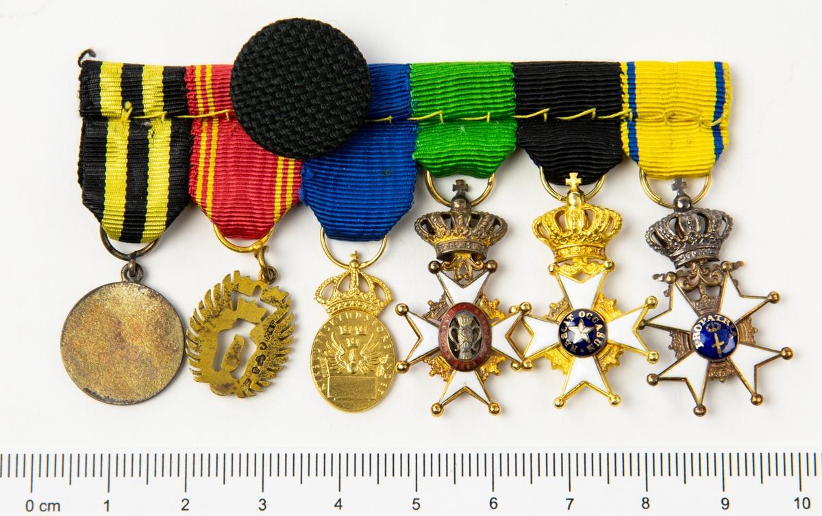 Sex stycken miniatyrmedaljer monterade på fästskena.