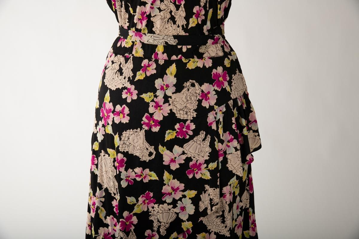 En svart kjole med et mangefarget motiv av blomster og en mann og en kvinne i ulike scener, begge kledd i 1700-talls overklasse-klær. Kjolen er ermeløs og krageløs. En glidelås under venstre arm går ned et lite stykke. Under denne er det et en splitt. Under halsen er det felt inn et svart gjennomsiktig stoff. Et hekte og en hempe i nakken skal lukke kjolen der, men hempe har røket  Det hører til et belte som er kledd i samme stoff.