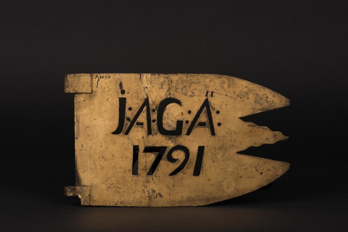 Treuddig vindflöjel av förgylld plåt. Flöjeln är genombruten med initalerna JAGÄ (Johanna Adolf Graver Älf) och årtalet 1791. Den mittersta udden är vågformad och det finns två fästen för fastsättning på stång.