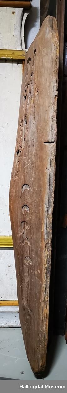 """Utskåren stav fra svalgang som har vært i Nes gamle stavkirke.  Stykket buler oppe på midten, slik at det dannes to trekanter med forholdsvis lav høyde på hver side, og to spisse trekanter med hypotenus opp og ned, hvor planken er tilspisset for å gå i spor. I venstre side spor med 3-kantet tverrsnitt.  I øverste trekant er akantusskjæring, godt bevart. Enkle profiler på sidetrekanter og nederste trekant i midtfelt.  Opp. i gml protokoll: """"Utskåren stav fra svalgang. Sies å være av Nes gamle stavkirke, nedrevet i 1864."""" Halvmåneformet hakk etter huggjern på høyre side. Noen skjæremerker i skurden."""