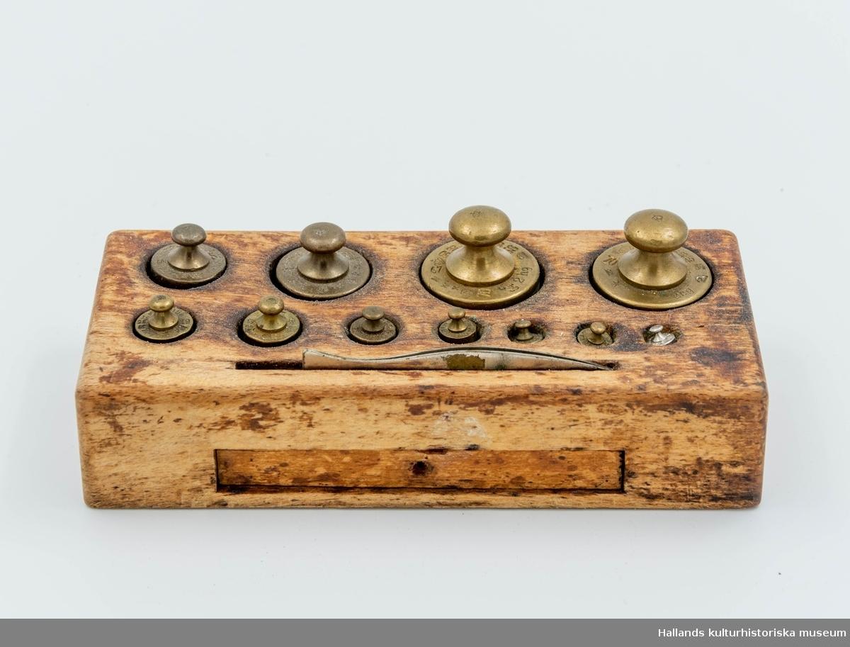 Lodvåg (precisionsvåg).a) Våg. Stativ och skålar i mässing. Underrede i trä. Bredd 50,5 cm, höjd 50,5 cm, djup 23,2 cm.b) Låda, höger. Bredd 20,7 cm, höjd 7 cm, djup 19,7 cm. Dragknopp i vitmetall.c) Låda, vänster. Bredd 20,7 cm, höjd 7 cm, djup 19,7 cm. Dragknopp i vitmetall.d) Kopp av mässing, höjd 6 cm, ø 5,5 cm.e) Kopp av mässing, höjd 6 cm, ø 5,5 cm,f) Viktsats. Längd 16,5 cm, bredd 7,5 cm, höjd 3,7 cm. 11 vikter + pincett.