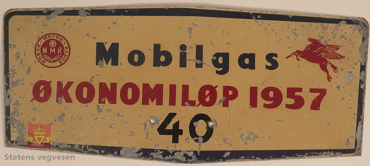 Hovedsakelig beige metallskilt. Det er laget til 2 festehull nederst på midten av skiltet. Påskrift: 40, Mobilgas, ØKONOMILØP 1957.