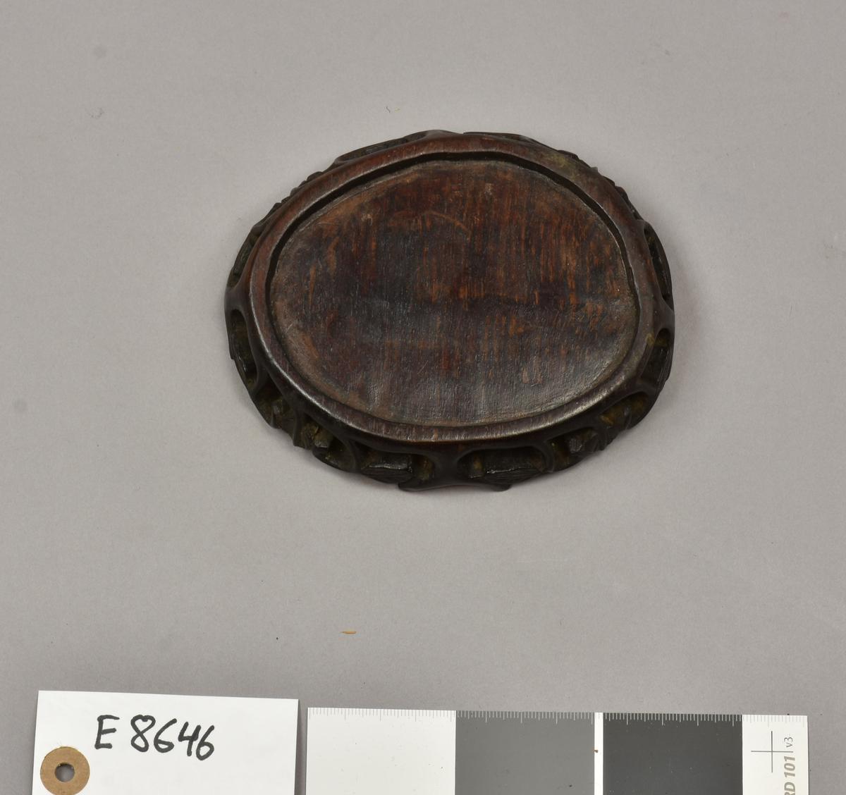 """E 8646 Fra protokollen: """" Sokkel av tre, oval. B: 13,1 cm, H: 2,6 cm. Kina, Øst-Asia."""""""