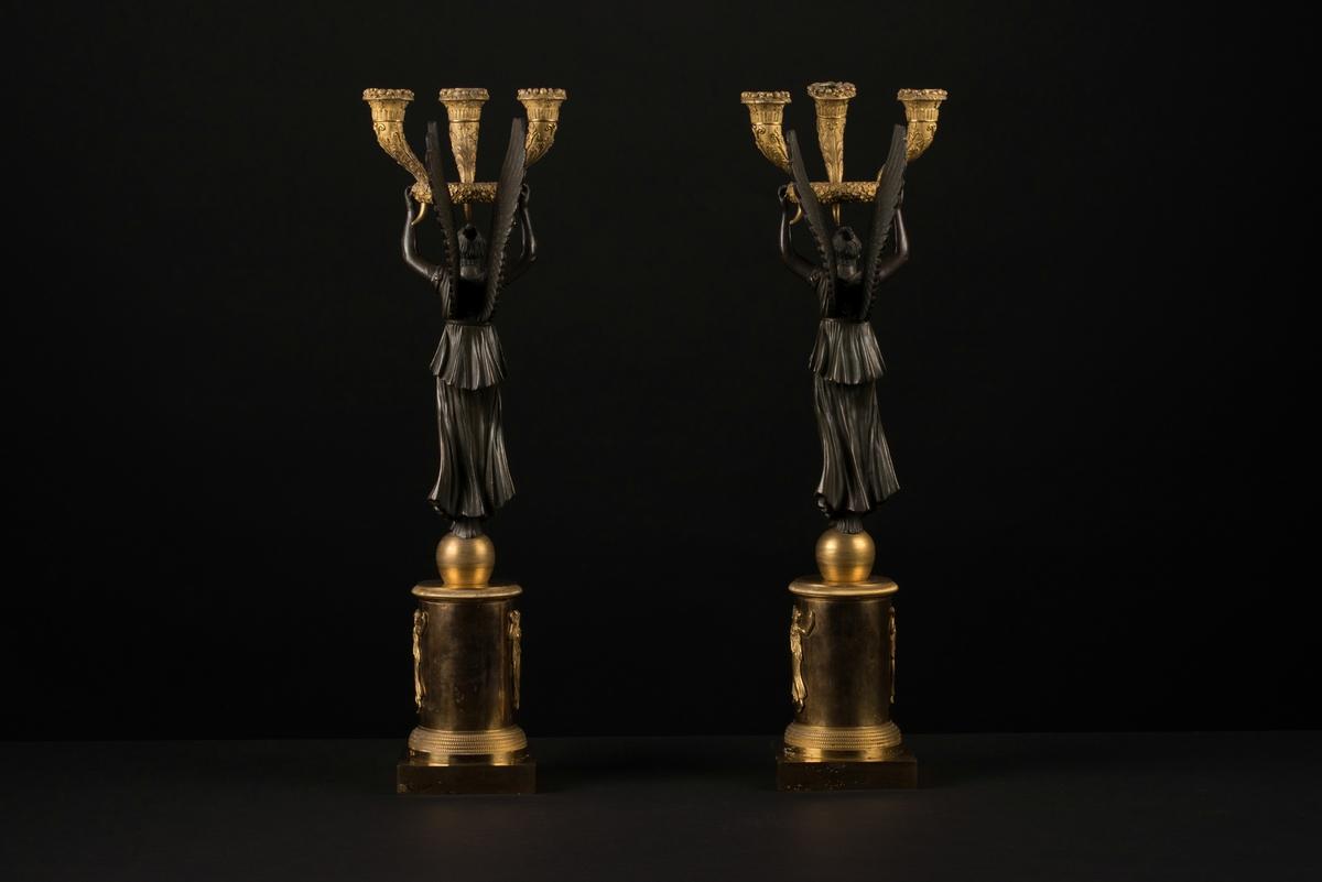 Ett par brännförgyllda bronsljusstakar, kandelabrar, med tre ljushållare vardera. En kolonnformad bas med ett klot på och en fyrkantig bottenplatta, av brännförgylld brons, bär upp en bevingad kvinna av svärtad brons. I de uppsträckta händerna sitter en krans med tre ymnighetshorn som utgör ljushållarna. Kransen och hållarna är även dessa av brännförgylld brons och dekorerade med akantusblad och vindruvsklasar.  Runt den runda bärande basen finns reliefer som föreställer tre dansande kvinnor, de tre gracerna, som håller i blomstergirlanger/festonger.