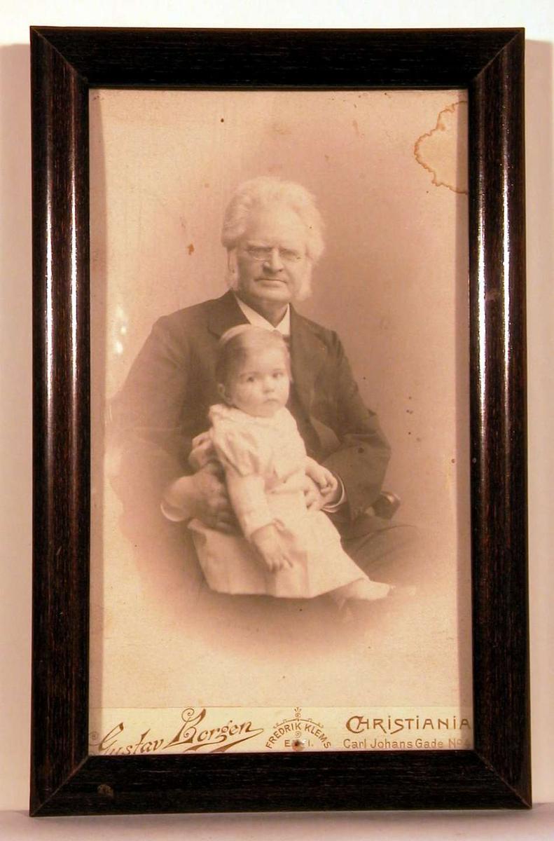 Atelierfortografi; portrettfoto av B.B. sittende med barnebarn på fanget.