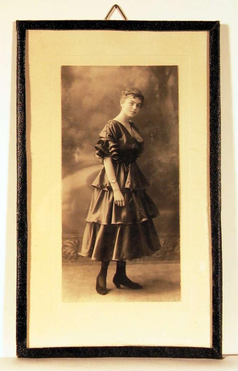 Atelierfotografi; helbilde av en ung dame i halvlang ballkjole med brede fleser i taft, sko med sløyfe og oppsatt frisyre. Bakgrunnsteppe viser en parksti kantet med trer og busker i solskinn.