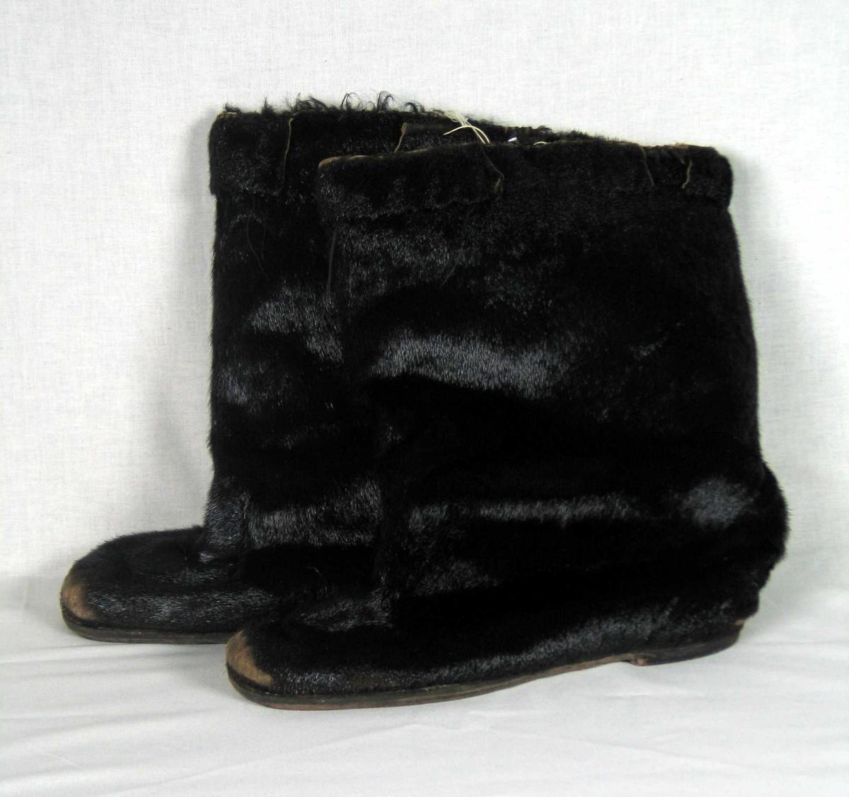 Støvler i pels, antatt av sel. Fôret med svart sauepels. Randsydd lærsåle. Lav pluget hæl, også stiftet.