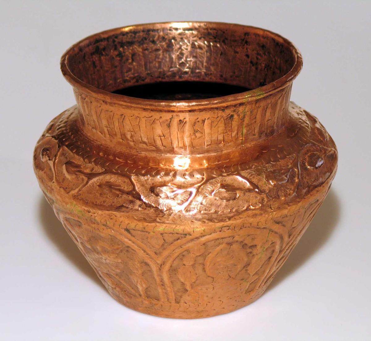 Urne i kobber med uthamret dekor i form av bladverk, dyr og hoder.