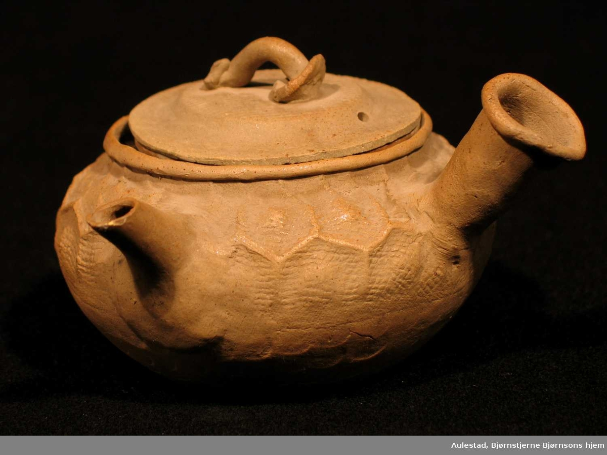 Liten tekanne i keramikk med løs sil og hul hank. Delvis glassert.