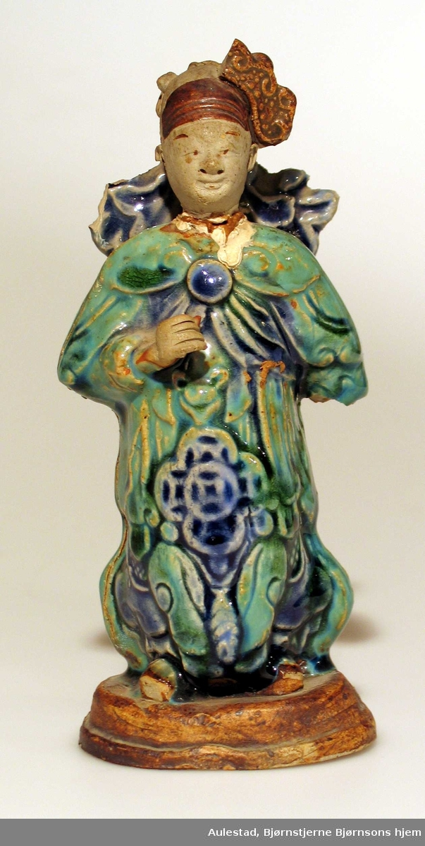 Porselensfigur i keramikk med ovalt fotstykke. Drakten har turkis, blå og brun farge.