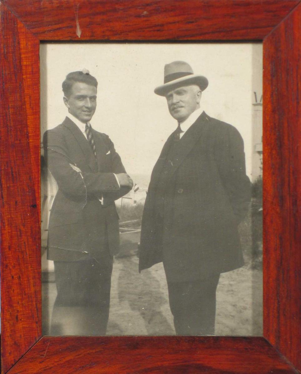 To dresskledde menn, den ene med hatt. Utendørs.
