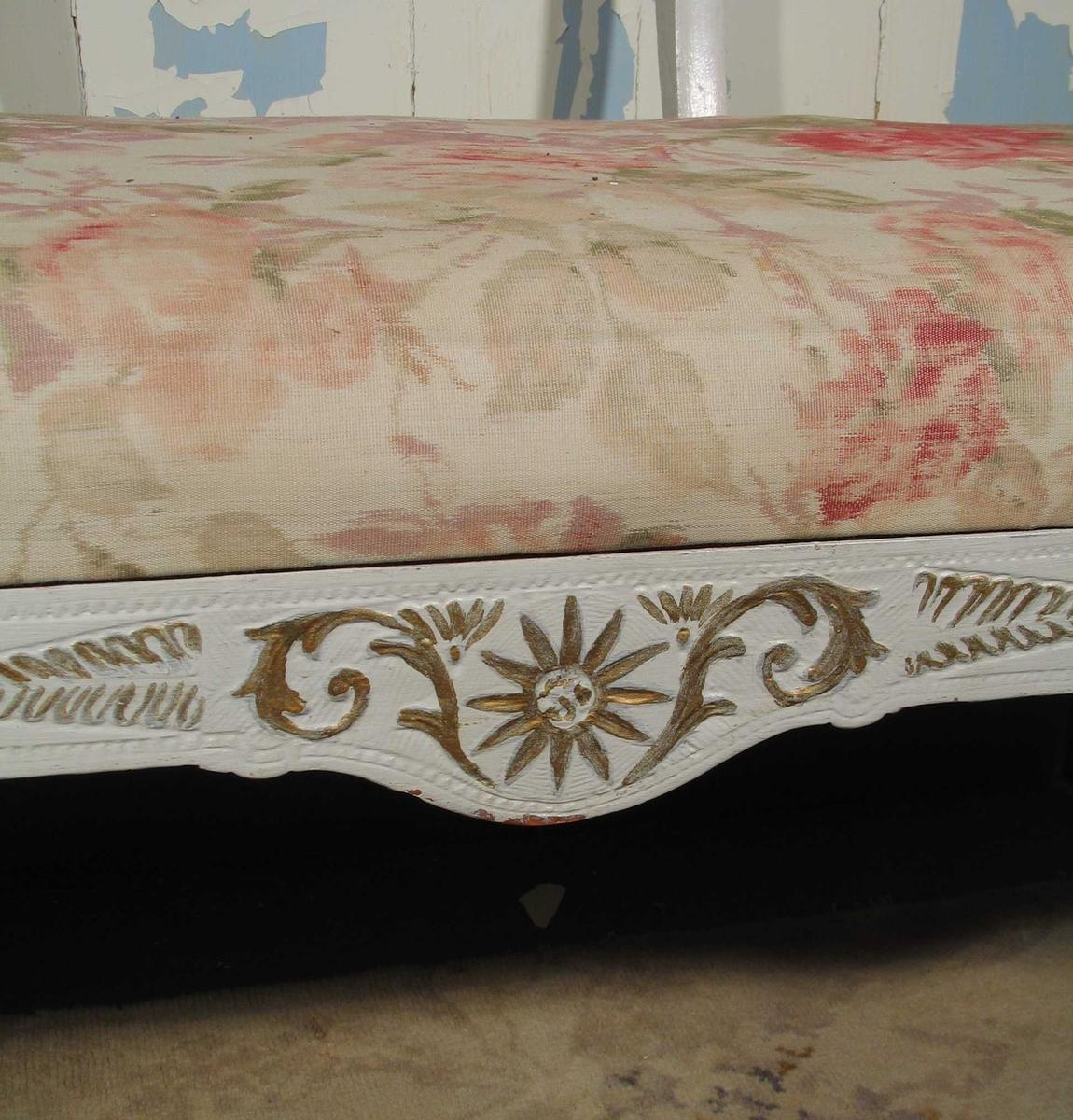 Benk i tre med utskjæringer på ryggstø, armlener og på sargen i forkant. Den er hvitmalt med gull i dekoren. Setet er trukket med blomstret kretong.