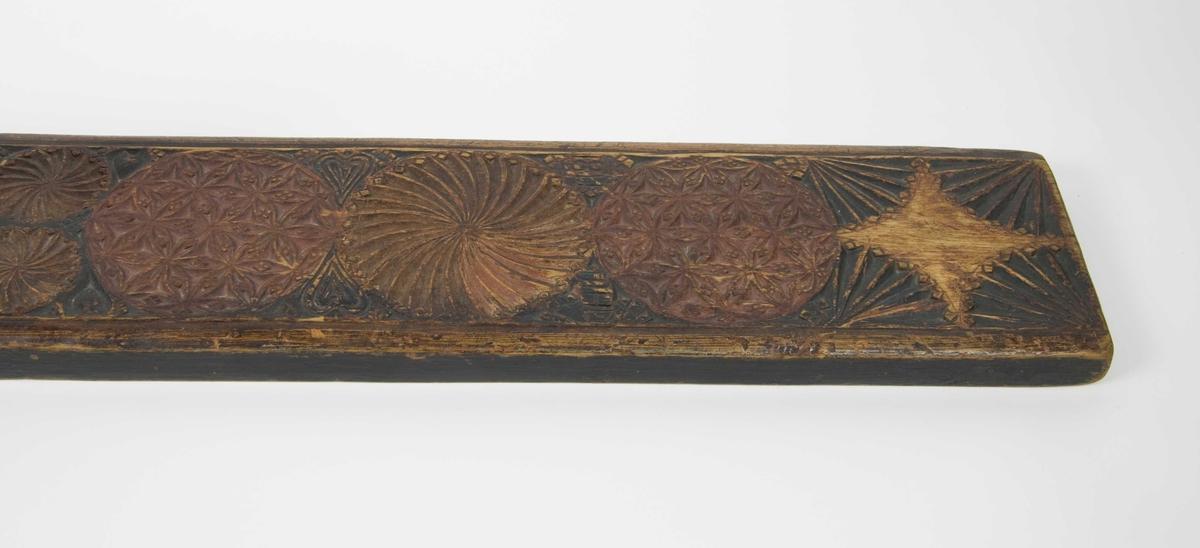 Små og store rosetter og vifteformer i karveskurd. Karveskurden er finmønstret.