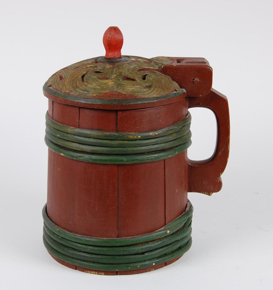Kanne av furustaver. Lokk med dype akantusutskjæringer, grønnmalt ring langs kanten. Kuleformet rødmalt lokkgrep. Rødmalt hank som er utskåret av en stav. Korpus rødmalt, fire grønnmalte gjorder opp og nede.