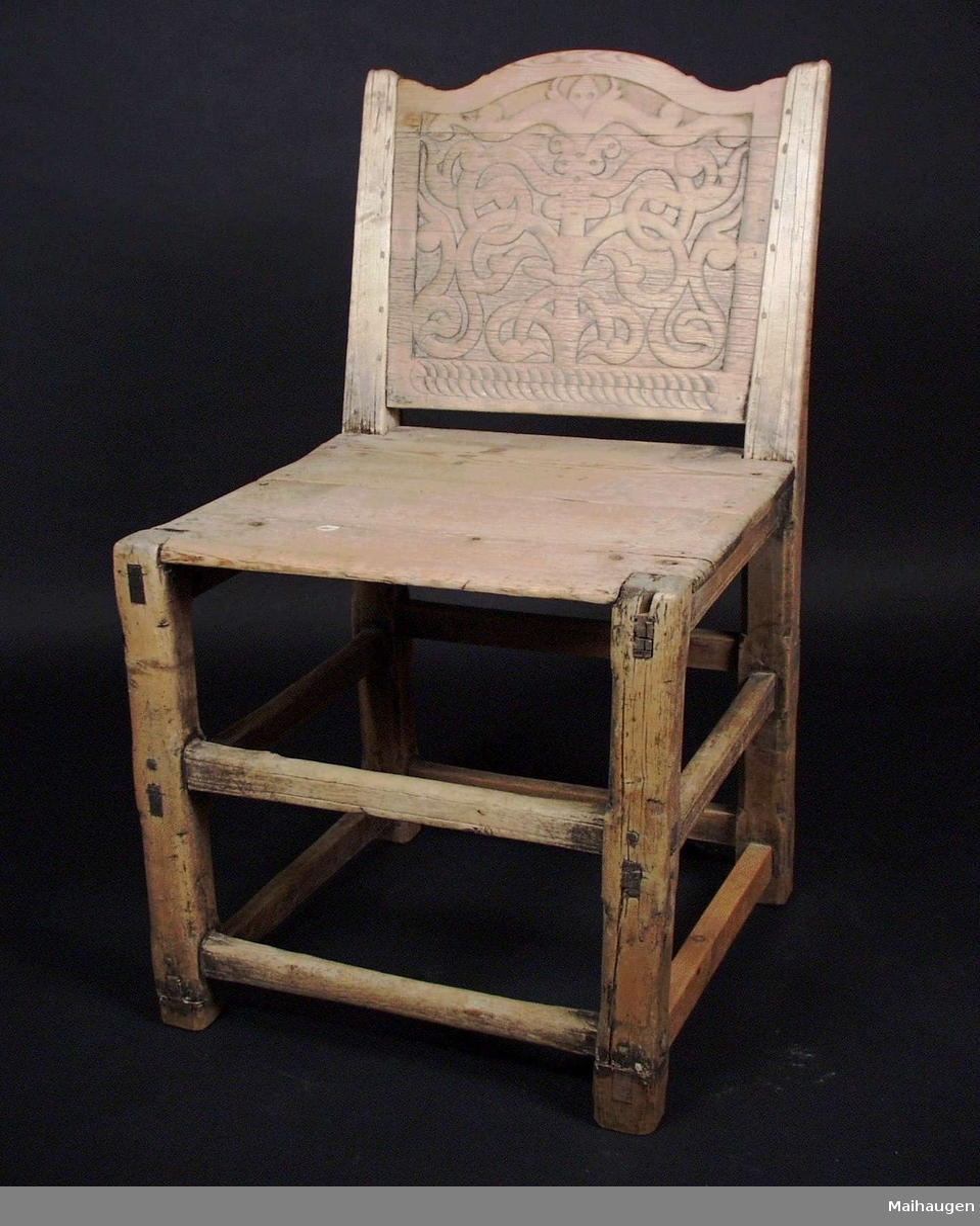 Stolen er av bjørk og furu med utskjæringer i rygg.