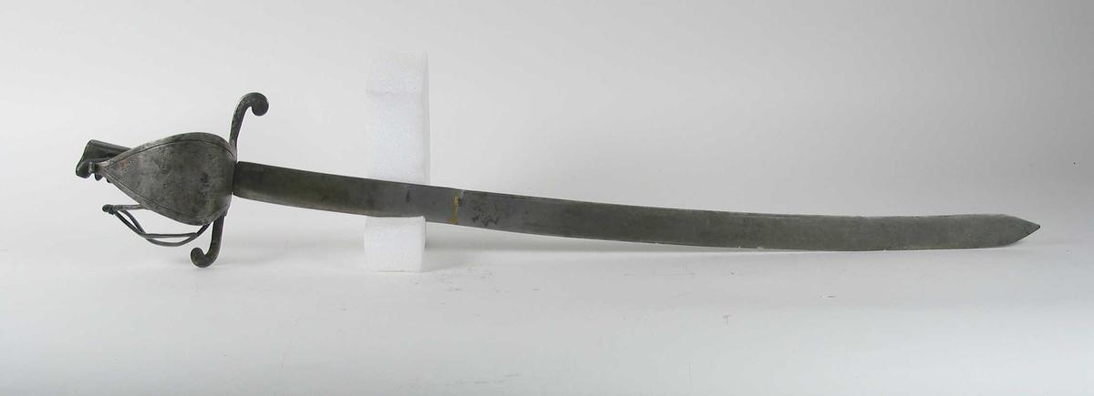 Trefliket knapp utformet som et dragehode. Asymmetrisk feste med oppbøyet trekantet parérplate på utsiden. Innsiden har klingebrekker og tombøyle. S-formede parérstenger som ender i en krøll. Festet er nyere enn opprinnelig produksjonstid. Tregrep med jernvikling. Enegget kileformet krum klinge. Klingen er brukket og skjøtt. Fremre del av klingen har en smal ryggstillt blodrand.