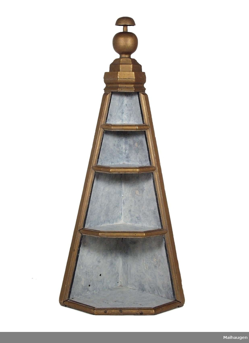 Hjørnehylla er malt i gullfarge med blått inne i hyllene, listekant er malt svart. Hjørnehylla har fire hyller, og en dreid kule på toppen.