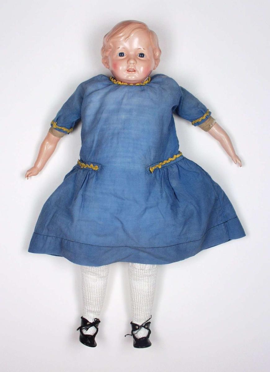 Dokka har hode og armer av celluloid. Resten er laget av stoff. Kjolen har påsydde kroklisser. Mamelukker og underkjole har blondekanter. Hjemmestrikkede knestrømper i rettstrikking med vrangbord.