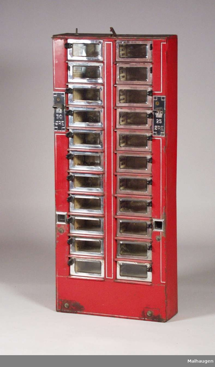 Rød sjokoladeautomat i metall med glassluker i to høyder, en for 30 og en for 25 øre. Lukene har krom innramming, og håndtakene er laget i bakelitt.