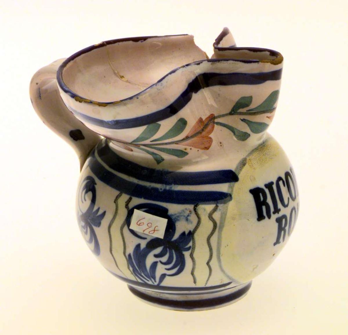 Liten mugge i keramikk. Muggen er limt og et stykke av kanten er slått av. Fargen er lys, med dekor i blått, gult, grønt og rosa. På korpus står det skrevet 'Ricardo Roma'.
