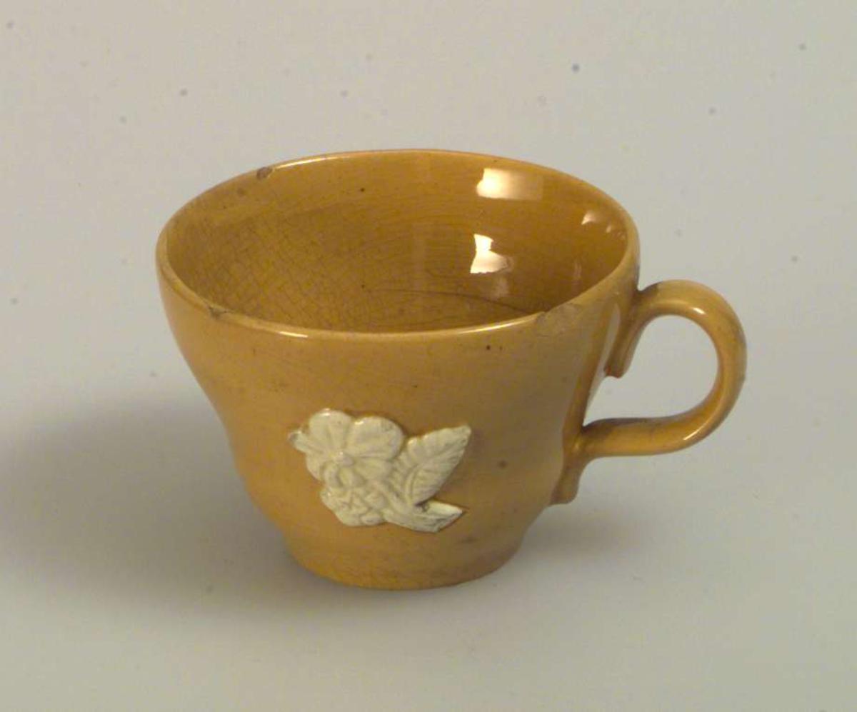 Gul kaffe-/tekopp med skål. Koppen er dekorert med en blomst med blad. Dekoren er hvit. Skålen er uten dekor. Det er hakk i både koppen og skålen. Det er ingen produksjonsmerker på kopp eller skål.