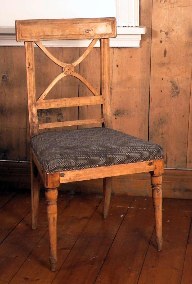 Trehvit spisestuestol med Andreaskors i ryggen og med stoppet sete. Stoffet i setet er blått og beige i et rutemønster. Trekket er skittent. Stolen er forsterket med jernbeslag. Det er slått et stykke av et av de dreide bena.