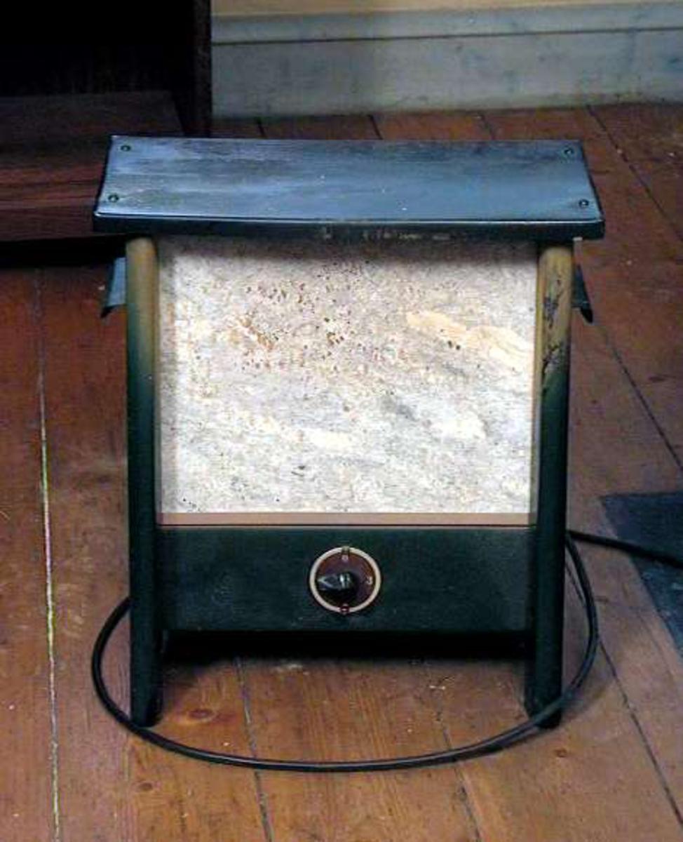 Elektrisk ovn med kleberstensplate i front. Ovnen er grønn, kabel og støpsel er sort. Bryter med innstilling fra 0 til 3.