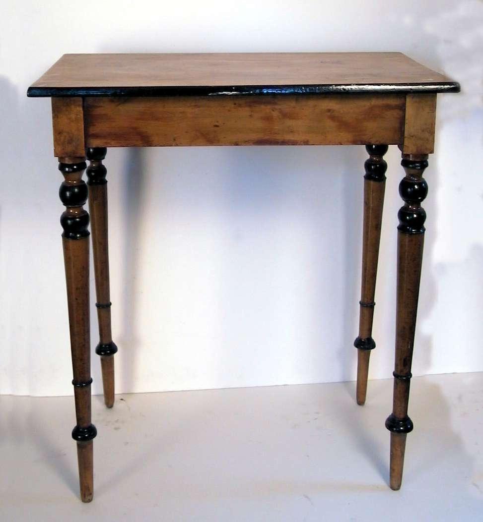 Bord med dreide ben. Bordet er lyslakkert med sorte kanter på bordplaten.