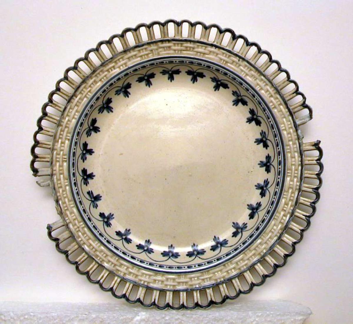 Tallerken med kremfarget glasur og blå, håndmalt dekor. Tallerkenen har hullfallskant ytterst. Biter av hullfallskanten mangler.