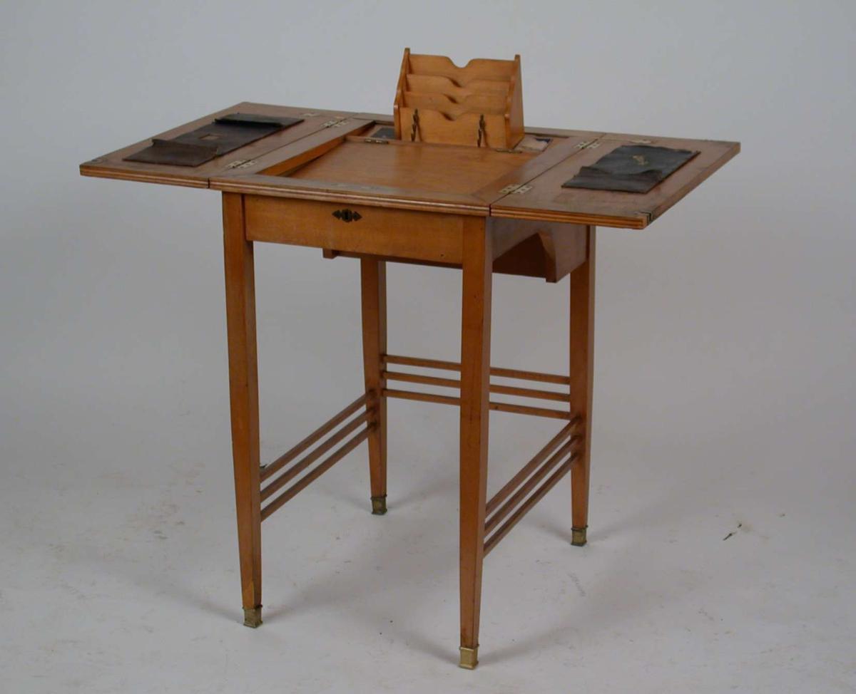 Et lite, firkantet sekretærbord med utbtrettbar skriveplate og brevholder. Platen og bena er av bjørkefiner.