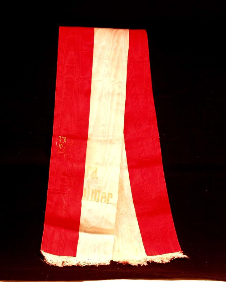 Bånd i rød og hvit silke. Båndet er delt i to. På båndet står det: Else Clara Volmer. De forgylte bokstavene er delvis avslitt.