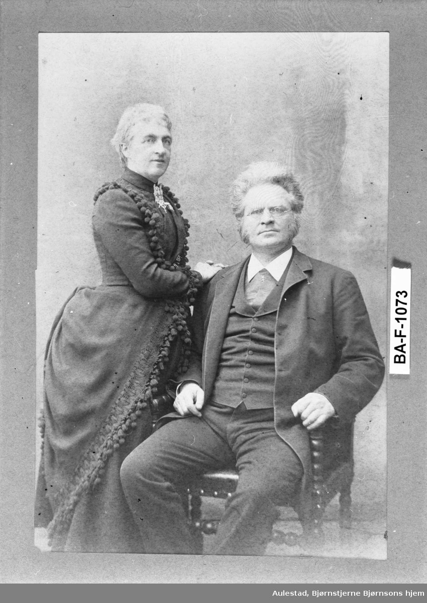 Fotografi limt på grå kartong med hvit rillet treramme og gullkant.