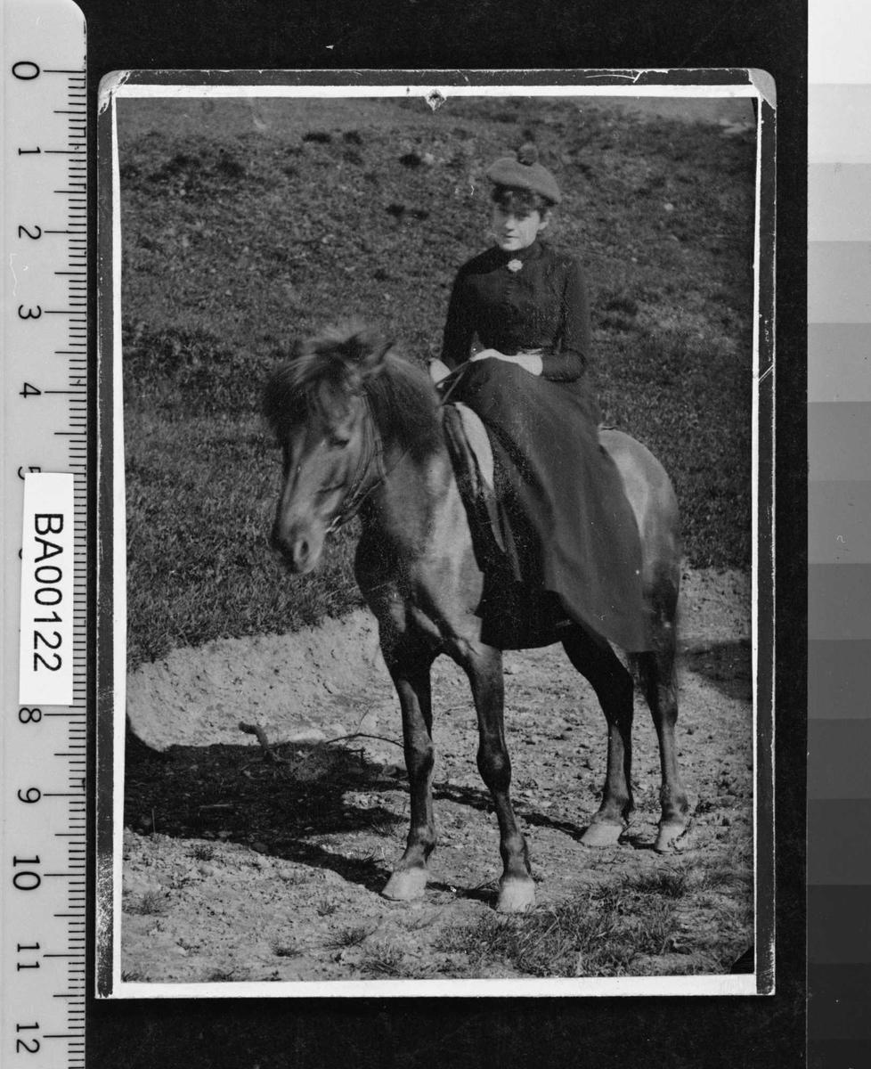 """Fotografi av ung dame til hest i damesadel, lang kjole og """"alpe-lue"""" med pompong på toppen."""