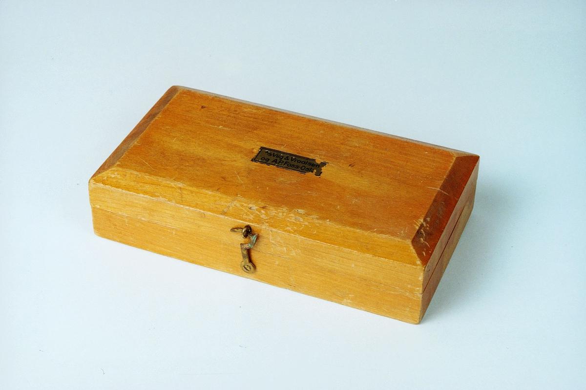 Loddkasse av bjørk og inneholder 7 lodder av messing på 250, 125, 100, 40, 20, 10 og 5 g