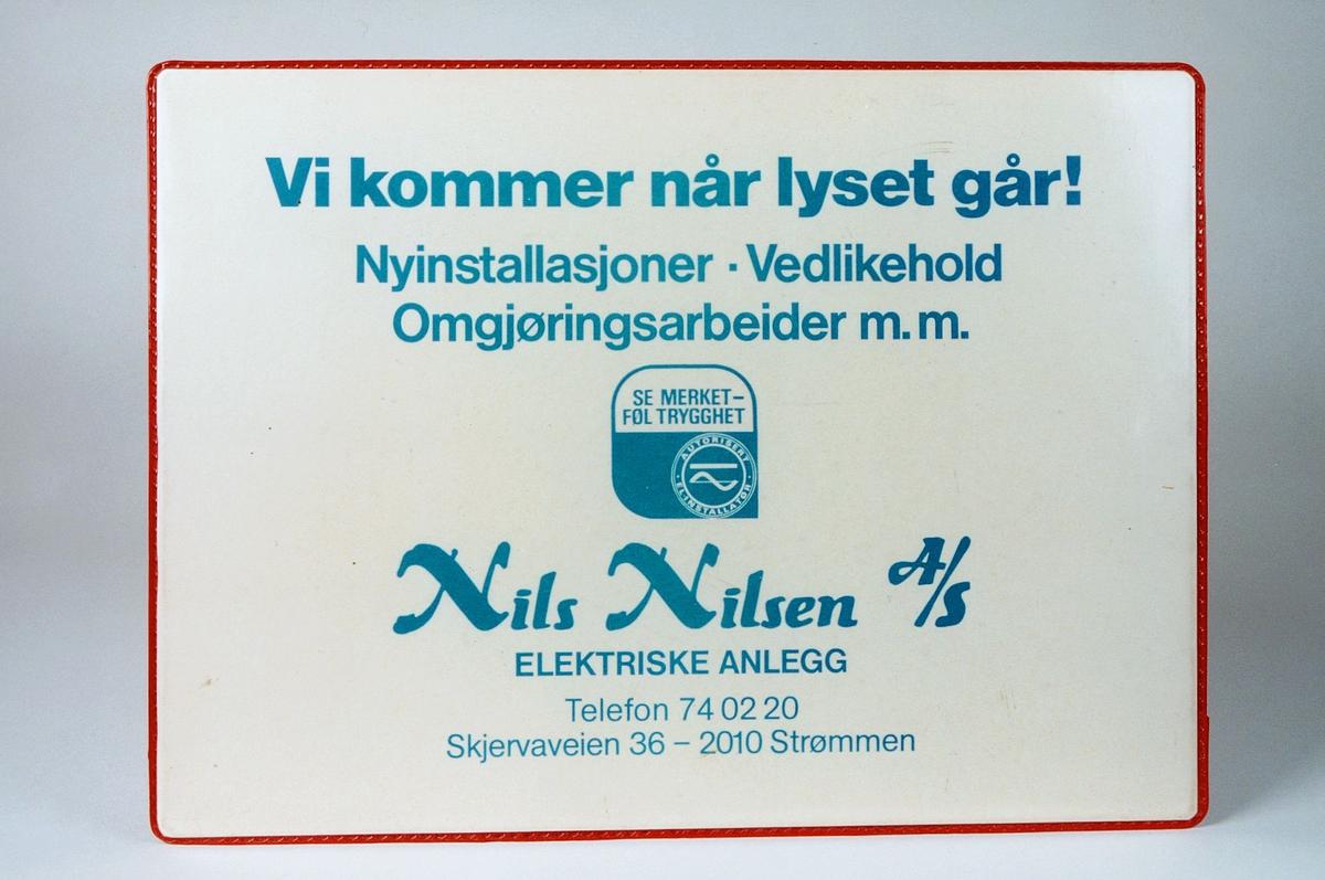 Postmuseet, gjenstander, skriveunderlag med reklame, Vi kommer når lyset går! Nils Nilsen A/S.