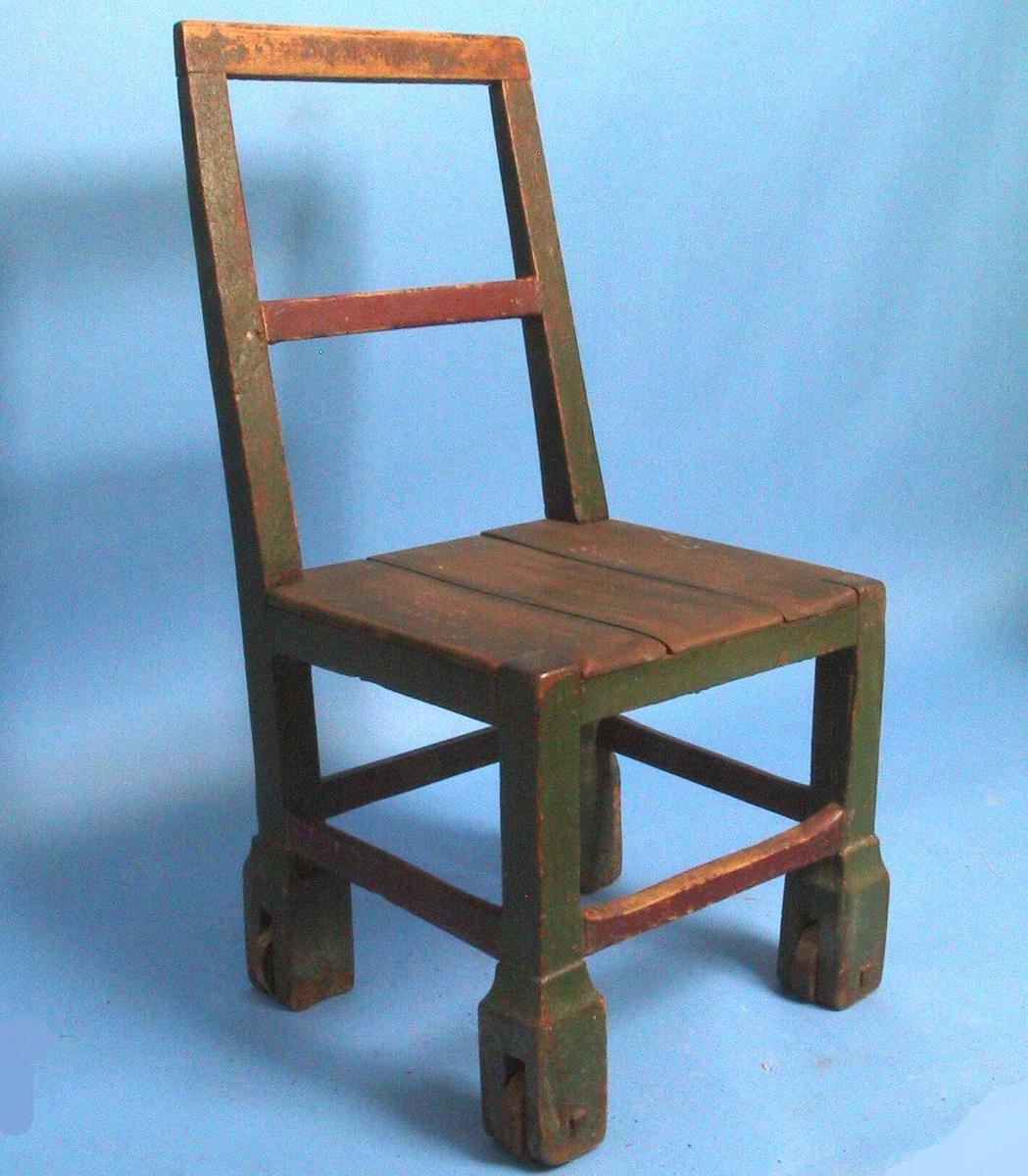 Rullestol av eik, malt mørk grønn og dyp rød. Ryggen har rektangulær ramme med en  midtsprosse. Dekorløs. Rette ben med utvidet nedre del, hvor dei er satt inn trehjul med trenagler. Stolen kan bare skyves sidelengs.  Malingen meget avslitt, bl. a. helt  i toppstykket. Sete mangler.