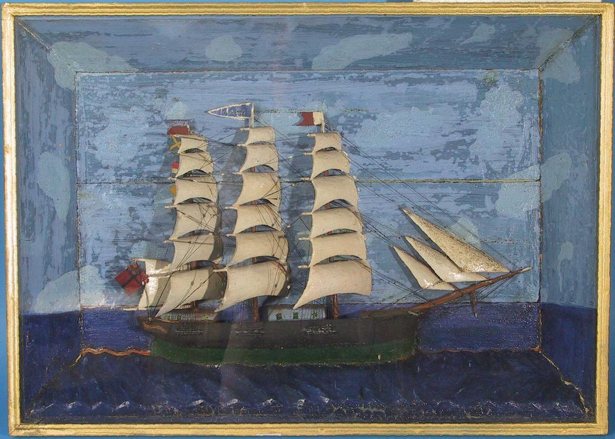 """Halvmodell i glasskasse av fullriggeren """"Saba""""  Sort   malt   tre  med grønt skrog. Hvitmalte treseil.  Kassen innvendig malt blå, mørkere i vannet,  over brunmalt kasse med forgylt list langs forkant. H. 49,7. B. 69,2. Dybde 9,1.  Tre master, i formast hvit og rød vimpel, i midt-  mast blå vimpel med utydelig navn """" SABA"""",  i bakre  mast rødt og blått splittflagg og en rad vimpler.  Akter det svensk-norske unionsflagget.  Tilstand mars 1967: litt store sprekker i bakplaten,  den   forgylte  listen litt avslitt."""