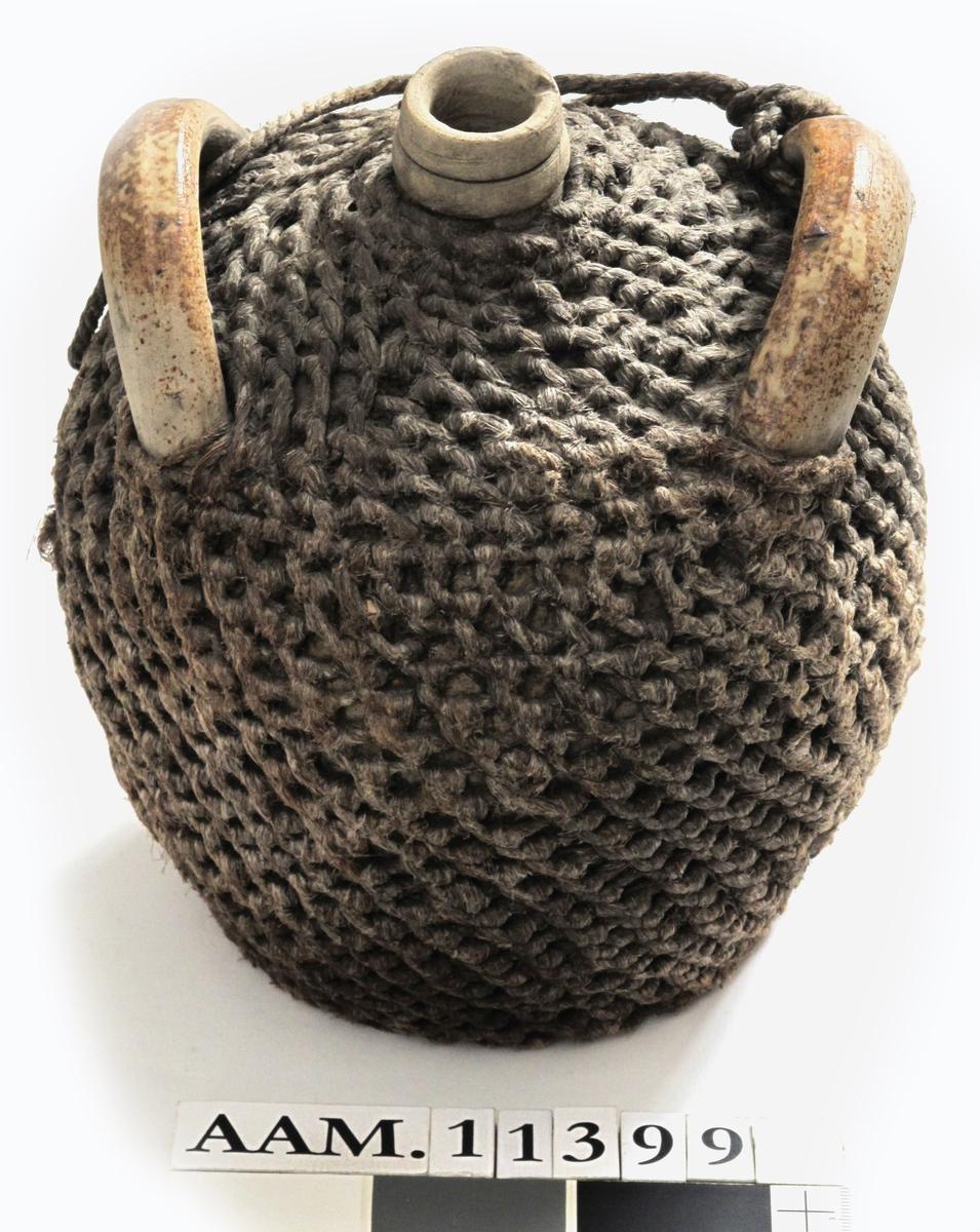 Geneverkrukke   brennevinsdunk  Rhinsk   steingods, hamp  efletning.  Bredbunnet rund krukke med smal munning,  to brede buede hanker over skuldrene.  Grågult gods med brun glasur i flekker.  Dekket av flettverk med en snor mellom  hankene. Godset er litt flatklemt på den  ene siden.  Tilstand: fletningen har et hull i bunnen,  hvor det  også er jordrester, har kanskje stått ute.