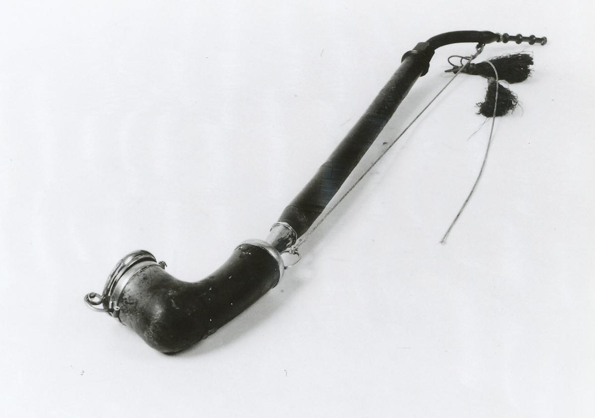 Hode m. lokk og beslag, skaft rettvokst, elastisk stykke, profilert munnstykke. Snor m. 2 dusker