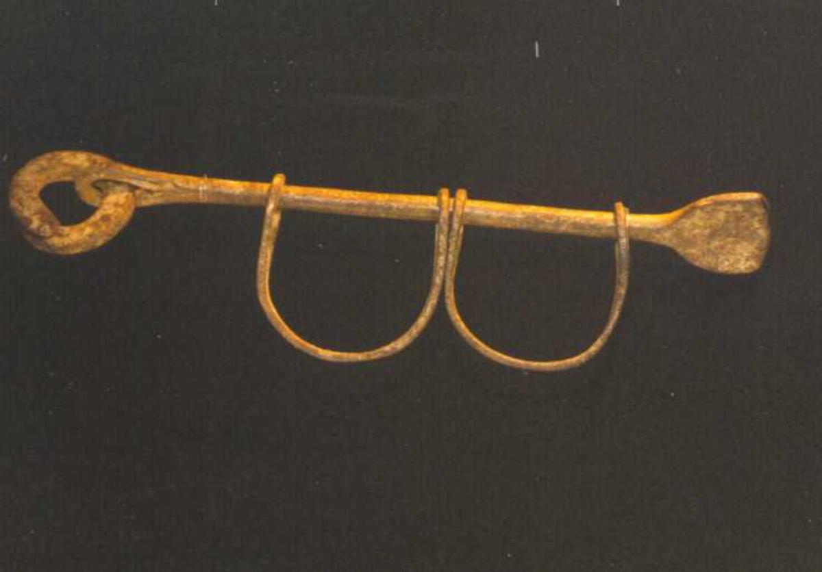 Jernstang m.to påtredde bøyler samt lås. Jernstanga er utbanket til et flatt stykke i den ene enden og til et øye i motsatt ende. I øyet er i satt en trang jernring som med verktøy kan taes av og på.