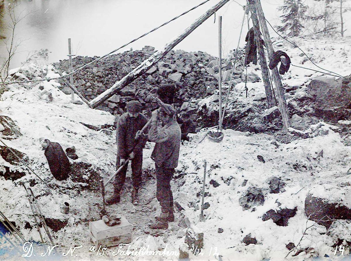 """""""03/12-1912"""" Nitriden. Utsprengning og planering av fabrikktomten. To karer holder på med minering. De slår annen hver gang på mineboret. Diverse redskaper. Heisanordning (stubbebryter med spill) for løfting av tyngre steinblokker."""