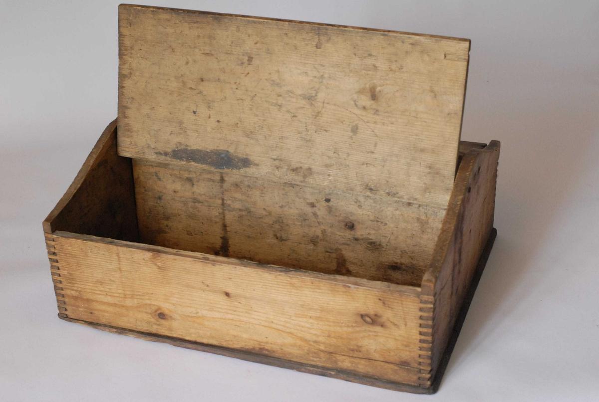 Form: Knivkassen har en rektangulær grunnflate. Hver kortvegg er et bord som buer oppover på midten, og her er midtbordet festet. Midtbordet utgjør skilleveggen innvendig og det stikker opp i en bue over lokkene. I denne buen er det skåret ut et håndtak. Bordene på langsidene er lavere enn dette. Hver halvdel er dekket av et lokk, som er festet til kortsideveggene med spiker og kan tippes opp.  Tilstand: Bunnen har to lange, gjennomgående sprekker. Innvendig, og forsåvidt gjennom hele bunnen, er det fuktflekker. Både innvendig og utvendig er det litt mugg. Ellers små sprekker, hakk og andre vanlige tegn på slitasje. Men hel.