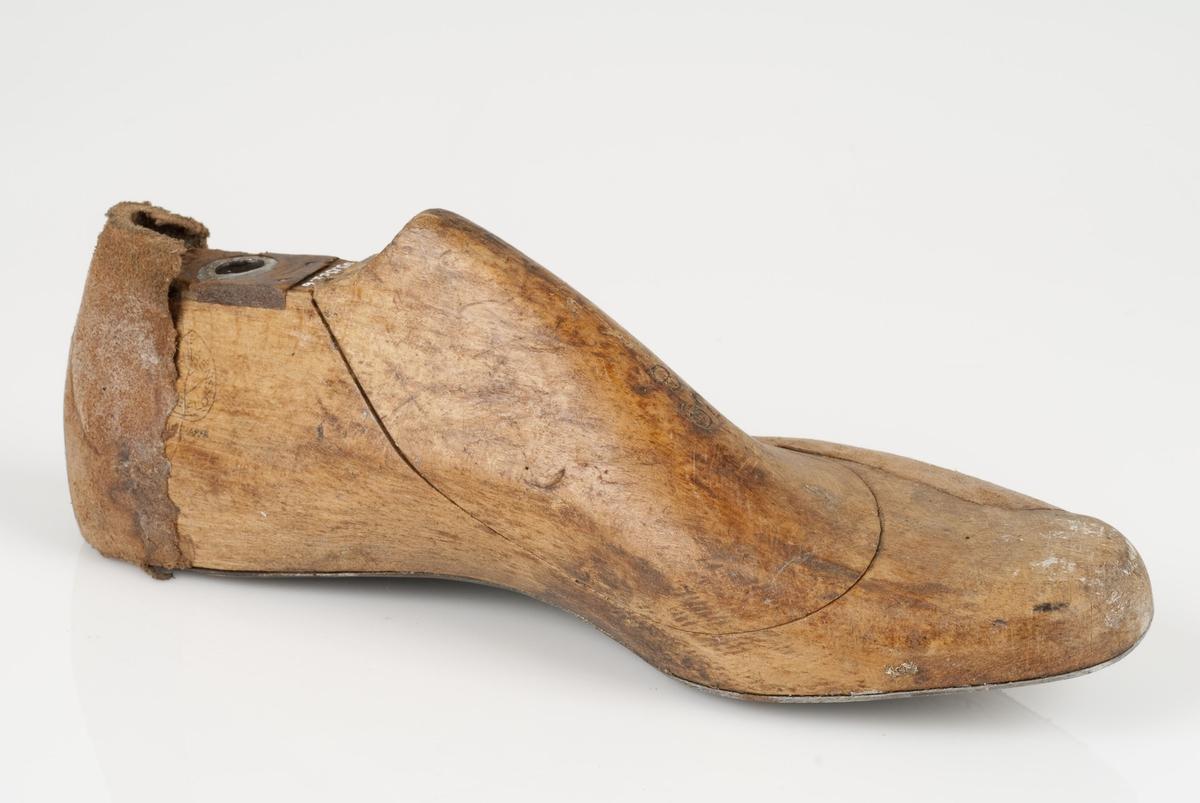 En tremodell i to deler; lest og opplest/overlest (kile). Venstrefot i skostørrelse 39, og 8 cm i vidde. Såle av metall. Lestekam av skinn. Lærhusk på lesten.