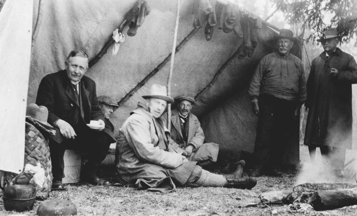 Fem menn under en presenning i ly for været.