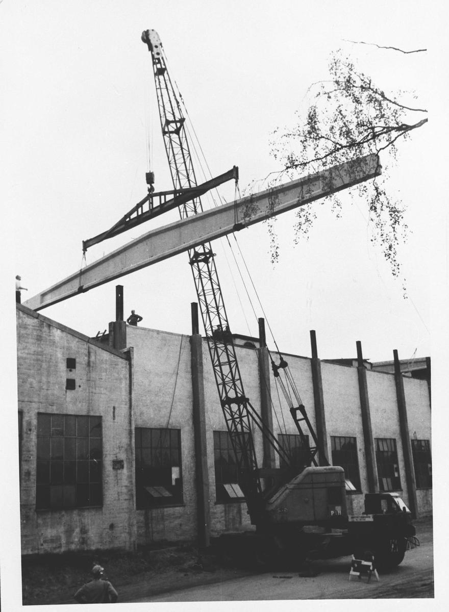 Ombyggingsarbeider ved Strømmens Verksted, byggningselementer, heisekran, arbeidere