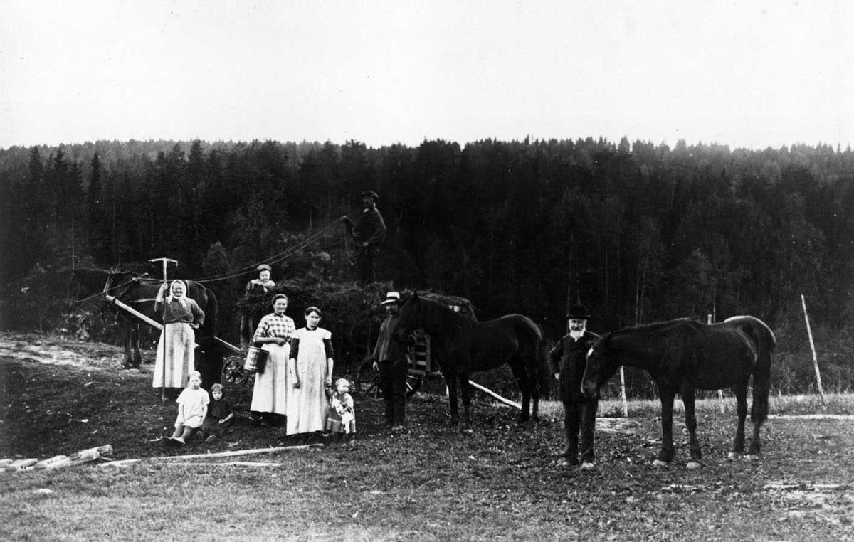 Slåttonn på Lahaug. Alle? gårdens folk samlet foran et høylass. I tillegg til hesten som trekker vogna, er det to løse hester.