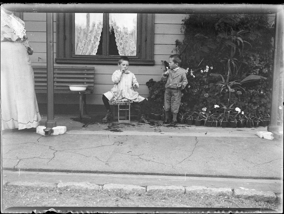 To av Christian Pierre mathiesen sine gutter foran et hus blåser såpebobler med pipe.